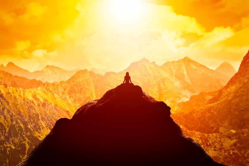Woman meditating on a mountain